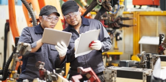 manufacturing workers with tablets for quality management system